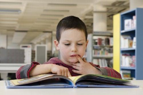 Niño con un libro para mejorar los procesos léxicos.
