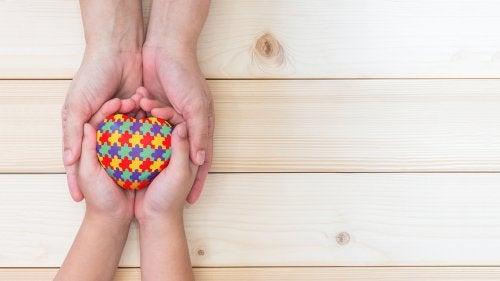 Niño sostiene en sus manos un corazón que simboliza el Trastorno del Espectro Autista.
