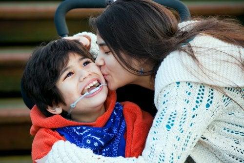 Madre besando a su hijo con discapacidad.