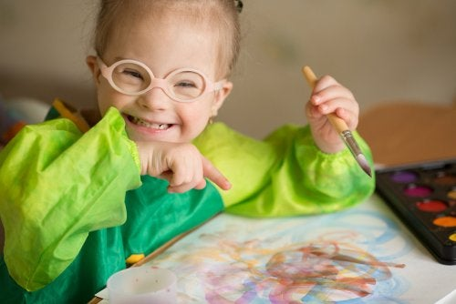 Niña con discapacidad haciendo un dibujo con acuarelas.