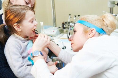 Niña en el pediatra haciéndose un examen para ver si tiene vegetaciones de oídos.