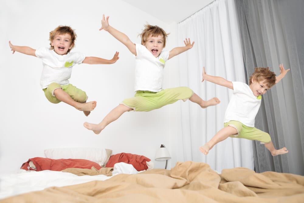 Un enfant qui saute sur un lit.