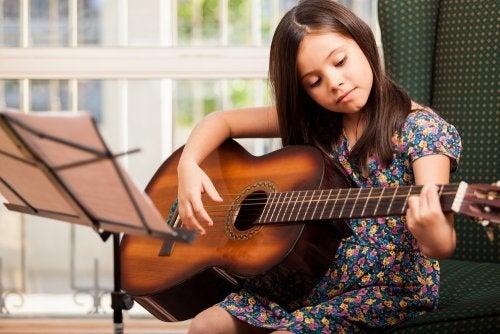 Niña aprendiendo a tocar la guitarra en una de las actividades extraescolares a las que asiste.