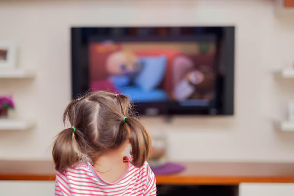 Une jeune fille qui regarde la télévision.