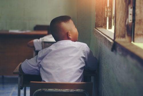 Niño en clase mirando por la ventana.