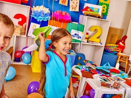 Niña con un avión de papel en el aula creativa con muchos colores.