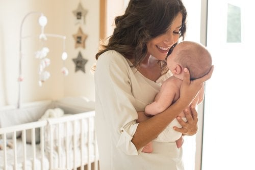Mamá cogiendo en brazos a su bebé para un buen desarrollo afectivo.