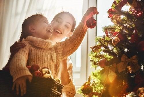 Madre e hija decorando el árbol de Navidad.