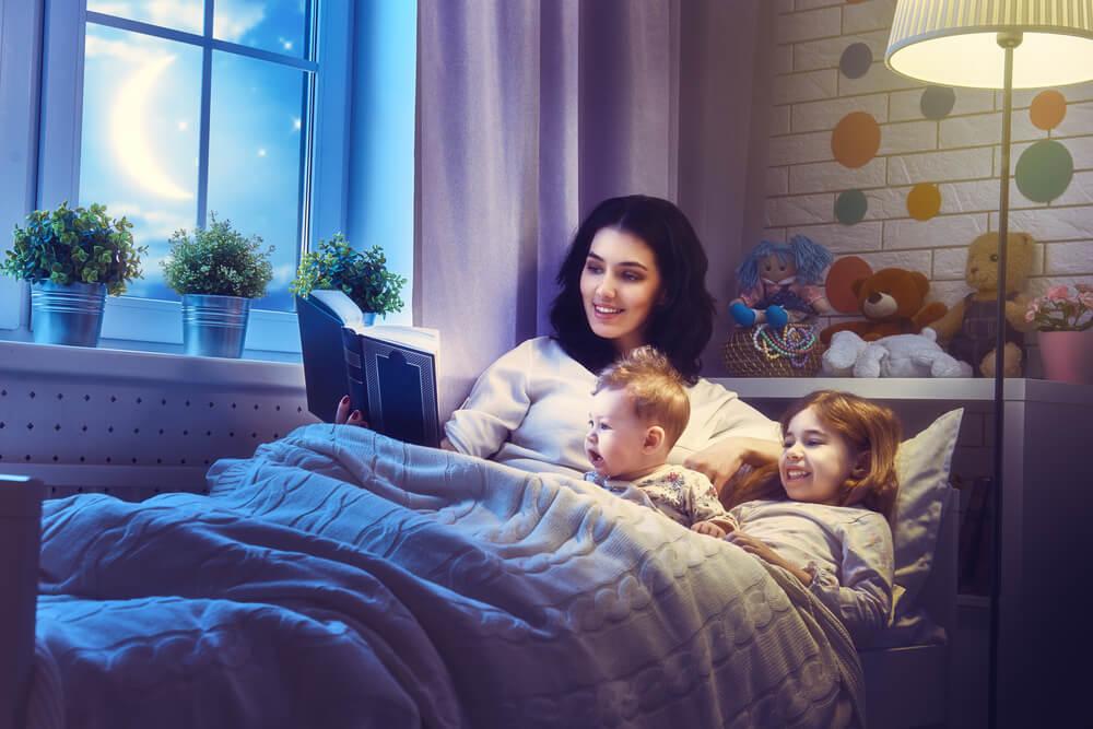 Une maman qui raconte une histoire à ses enfants au lit.