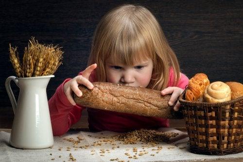 Niña con sensibilidad al gluten no celiaca con un pan entre las manos.