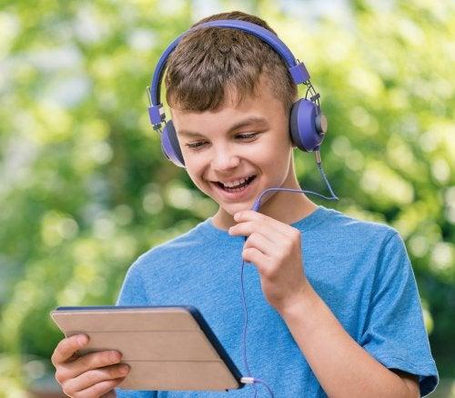 Niño hablando por la tablet al aire libre.