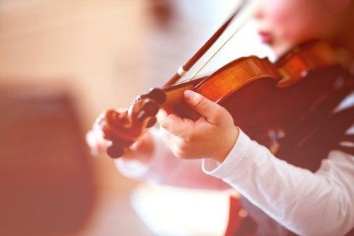 Niño tocando el violín en clase de enseñanzas artísticas.