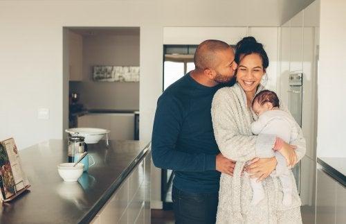 Padres pareja de hecho abrazando a su hijo recién nacido y sabiendo los datos curiosos sobre le desarrollo de los niños.