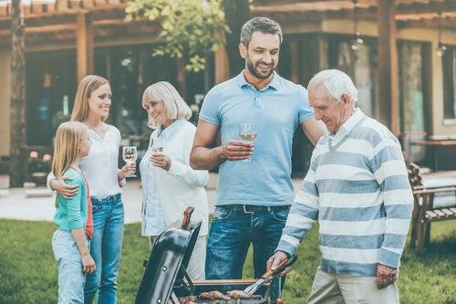 Familia pasando las vacaciones de verano en casa de los suegros y haciendo una barbacoa.