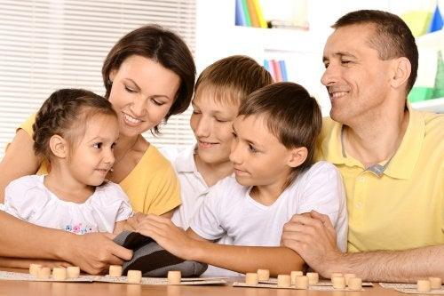 Padres con sus hijos jugando a juegos para mejorar la ortografía en familia.