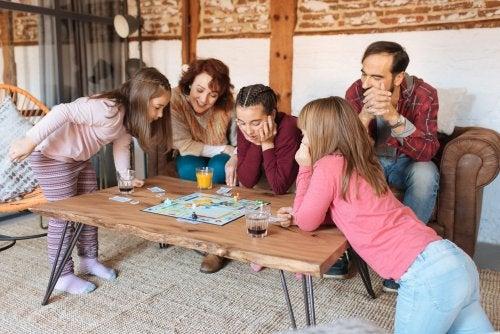 Familia jugando a juegos de mesar pero sin dejar ganar a sus hijos.