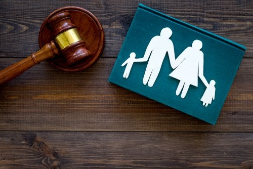 Juzgado de familia representado por un mazo y un dibujo de unos padres con sus hijos.