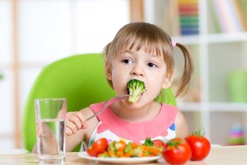 Niña comiendo un plato de frutas y verduras con una buena nutrición infantil.