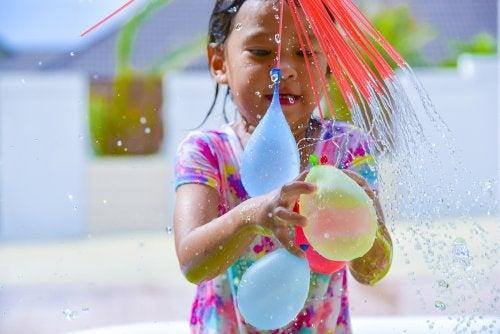 Niña con globos de agua preparando juegos para divertirse.