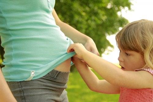 Niña curiosa mirando la barriga de su mamá embarazada.