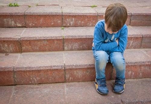 Niño que sufre acoso escolar o bullying sentado en unas escaleras solo.