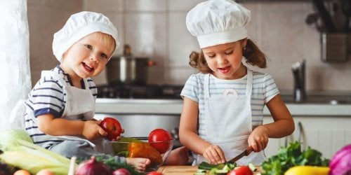 Niños en la cocina preparando diferentes comidas.