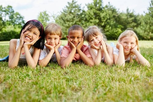 Niños con una educación intercultural tumbado en el césped.