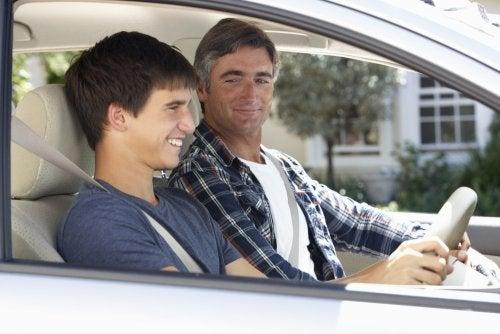 Padre enseña a conducir el coche a su hijo.