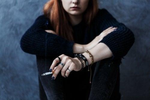 Adolescente rebelde fumando un cigarro porque su padres son muy restrictivos.