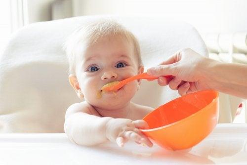 Niño comiendo cucharada de comida y agarrando el plato con la mano.
