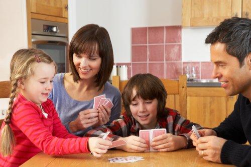 Familia jugando a las cartas sin dejar ganar a su hijos.