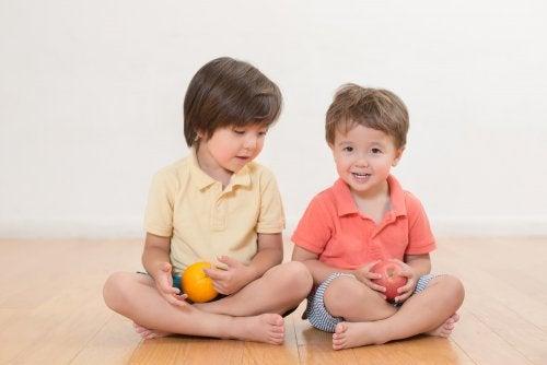 Hermanos sentados en el suelo con una fruta de la mano.