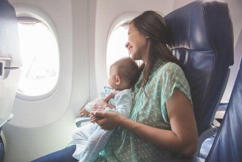 Mamá con su bebé en brazos en el asiento del avión.