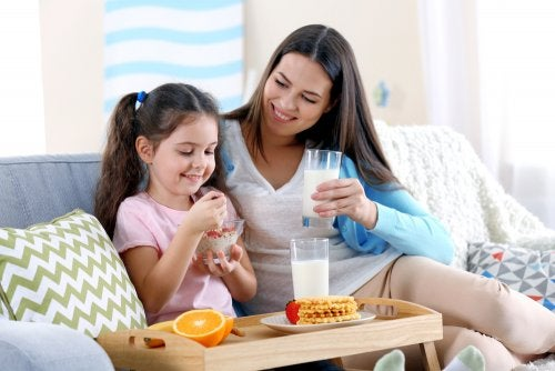 Madre e hija merendando fruta y algunos productos lácteos.