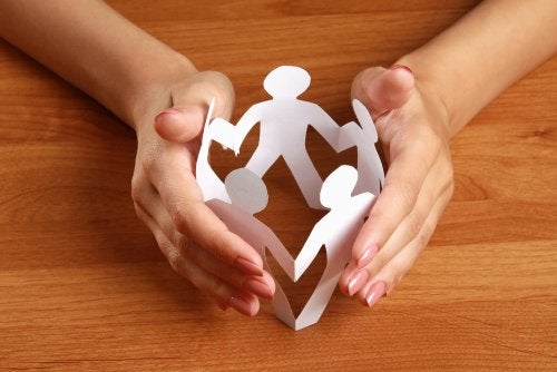Mano alrededor de la silueta de cuatro personas hechas con papel simulando una empresa familiar.