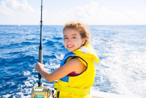 Niña navegando por el mar con el chaleco salvavidas.