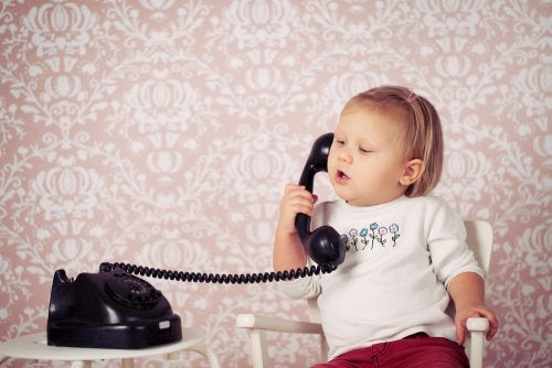 Niña bebé hablando con un teléfono antiguo para el desarrollo del lenguaje.