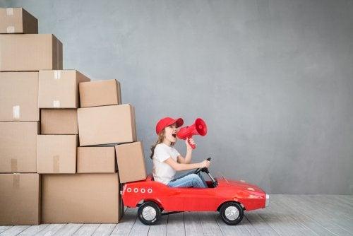 Niña jugando con un coche y un montón de cajas a modo de jefa de la empresa familiar.
