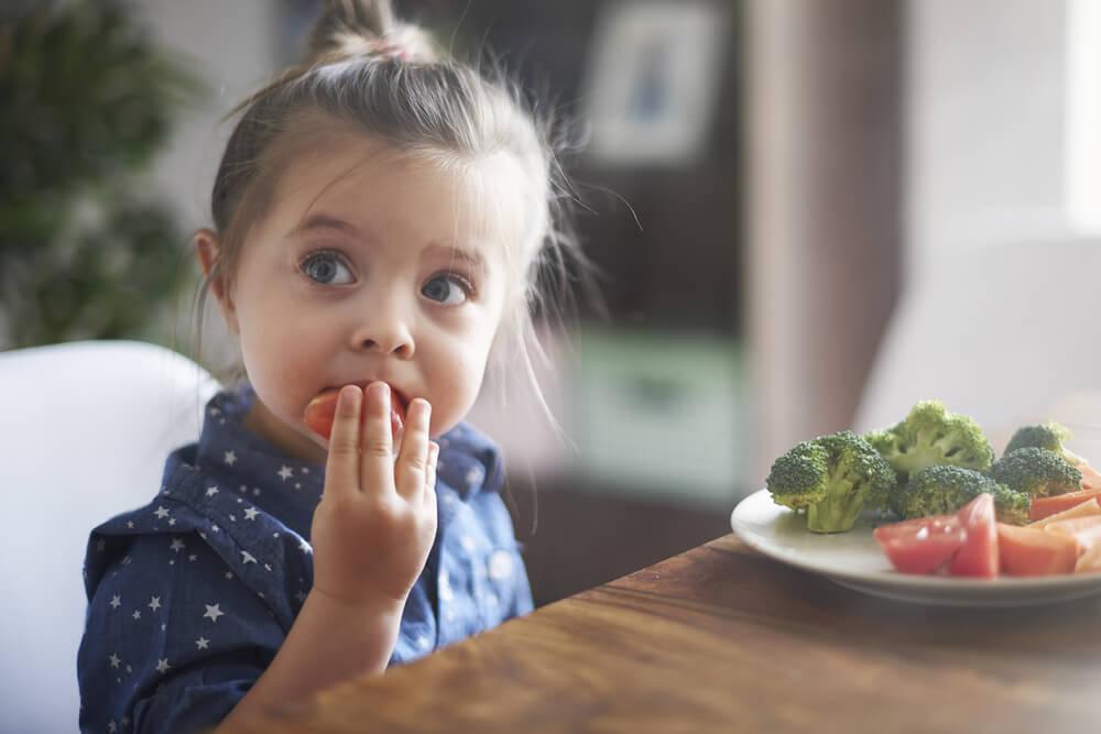 Niña comiendo en la mesa frutas y verduras.