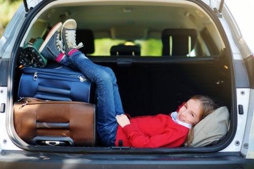 Niña metida en el maletero del coche antes de partir hacia su viaje al extranjero.