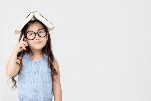 Niña con un libro en la cabeza poniendo en práctica el aprendizaje basado en el pensamiento.