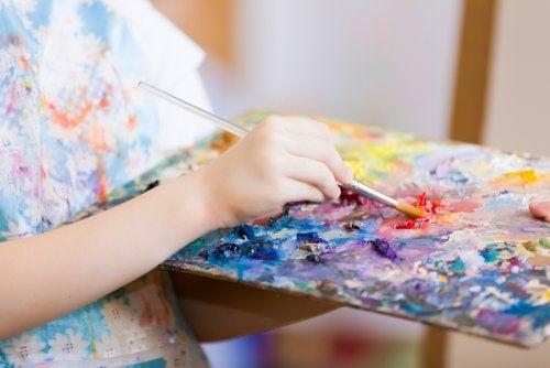 Niña pintando un cuadro trabajando las inteligencias múltiples en el aula.