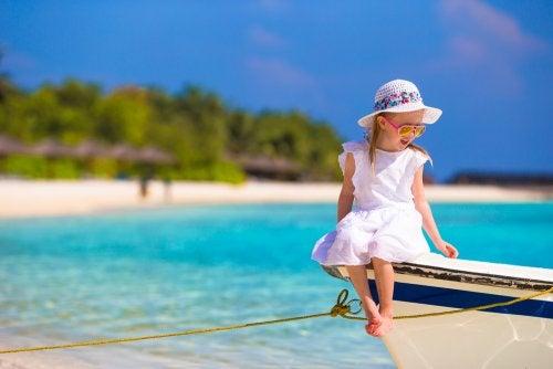 Niña sentada en un barco en la orilla de la playa a punto de salir a navegar.