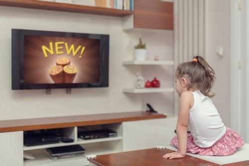 Niña viendo en la televisión anuncios publicitarios.