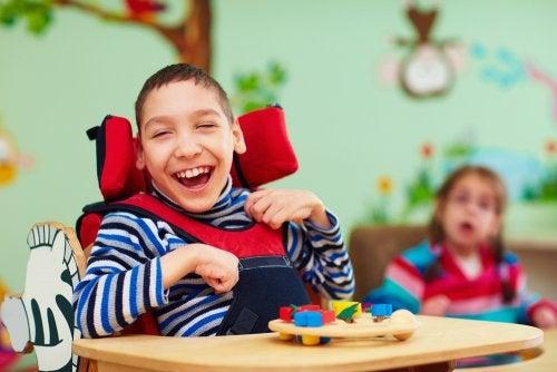 Niño con discapacidad motora en clase muy sonriente.