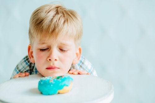 Niño mirando con pena un donut porque no puede comerlo debido a su intolerancia al gluten.