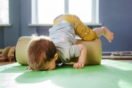 Niño jugando en la colchoneta en sala de psicomotricidad.