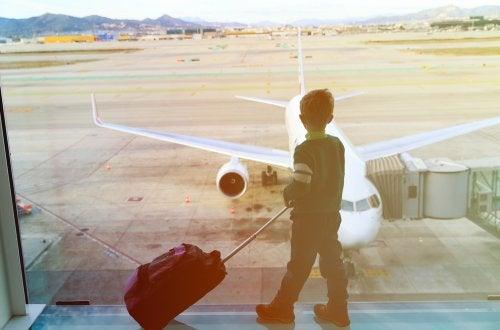 Niño mirando por la ventana del aeropuerto los vuelos que llegan.