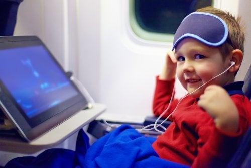 Niño viendo una película en el avión durante su vuelo para ir de vacaciones.