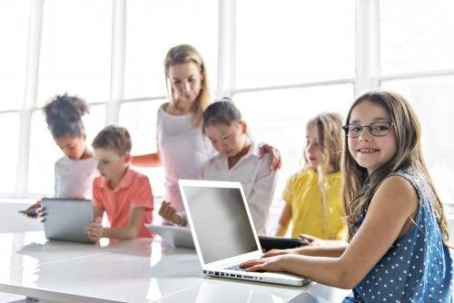 Alumnos en el rincón del ordenador del aula con la profesora.